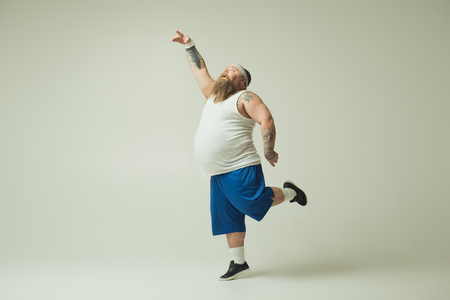 Feeling like a bird. Inspired fat man is dancing with grace and serenity. He is raising hand up while standing on one leg
