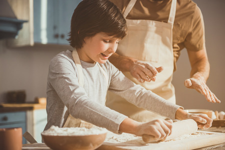 Man and boy enjoying cooking of pastry together. Child rolling out dough on processing board while dad explaining Stockfoto