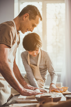 Father standing in apron and unrolling soft dough on table while his kid observing process. They are smiling