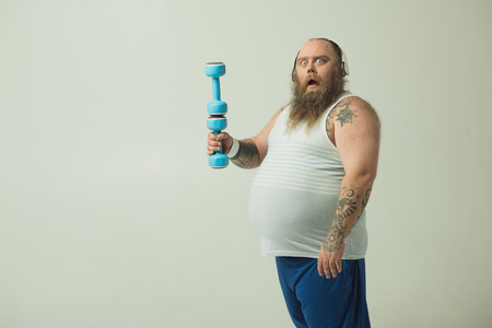Portrait of surprised fat man holding a dumbbell on another on. He is standing and looking at camera with shock while wearing earphones. Isolated and copy space