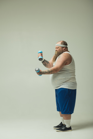 Eager fat man is lifting dumbbells with effort. He is standing in sportswear. Copy space