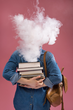 Excess of information. Female student has smoke over her head. She is standing and holding lots of books. Isolated