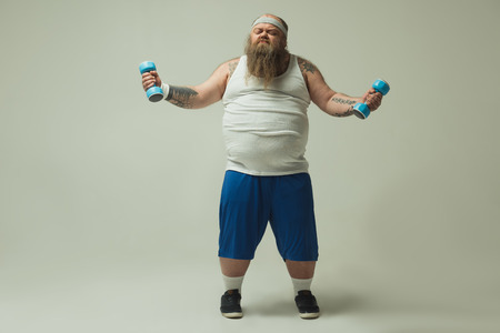Full length portrait of severe fat sportsman lifting dumbbells with effort. Weight loss concept