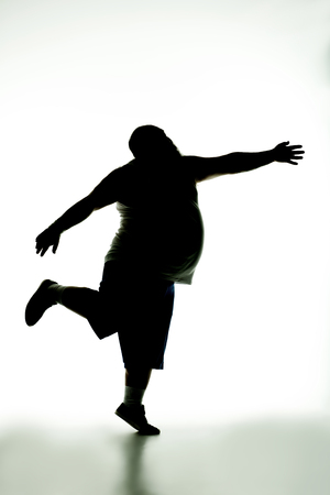 Hungry fat man is running with a rush to something. He is waving hand in move Stock Photo