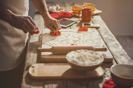 Close up of man hands excising cookies with cute cutters from plastic mass. Ingredients and inventory are on table Stockfoto