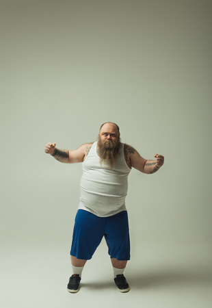 I am strong. Full length portrait of confident fat man is straining his muscles while standing in sportswear