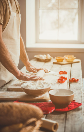 Adult guy unrolling soft pastry for carving cookies. Window on background. Close up