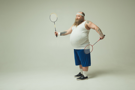 Full length portrait of joyful fat man holding tennis rackets. He is standing and smiling. Copy space