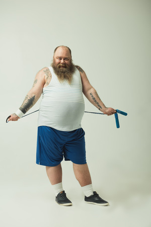 Full length portrait of carefree fat man is keeping skipping rope behind his back. He is looking at camera with joy and smiling Banco de Imagens