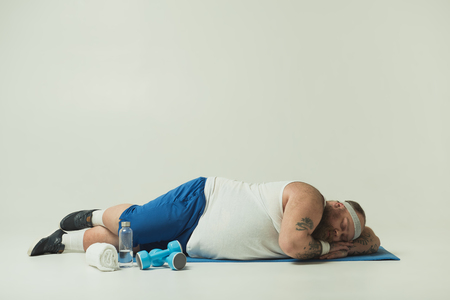Sluggish fat man is sleeping on sport mat instead of training. Dumbbells and bottle of water on floor