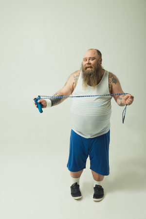 Lets jump. Full length portrait of funny fat man is holding a skipping rope. He is looking at camera and smiling