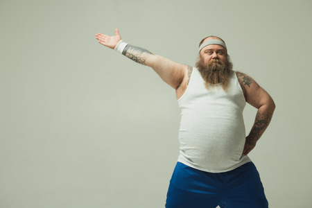 Portrait of cheerful thick guy going for sports. He is standing with arm akimbo while stretching another hand sideways. Isolated and copy space Banque d'images - 100915630