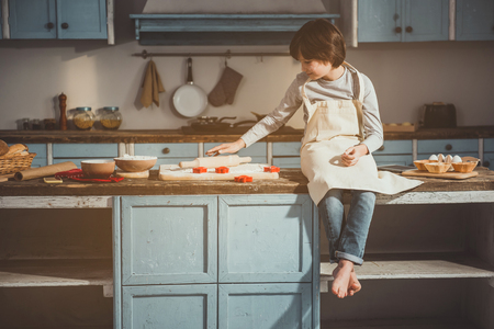 Child sitting on wooden desk in kitchen. He is taking rolling pin. Cooking inventory and ingredients are on table