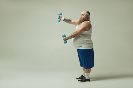 Side view profile of cheerful fat guy with big abdomen exercising with dumbbells. He is looking at camera with amazement. Copy space Stock Photo