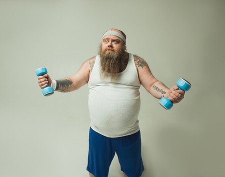 Strained fat man is exercising with weights. He is standing and holding sports equipment with exertion. Isolated