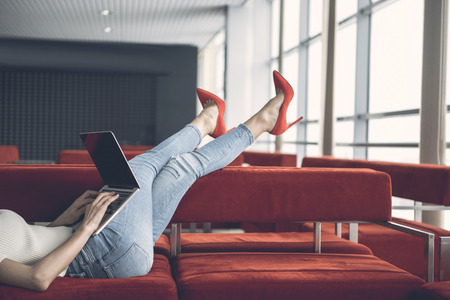 Girl using modern digital device while resting on sofa indoor