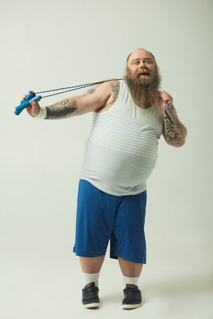 Portrait of cheerful thick guy is having fun with a jump rope and laughing