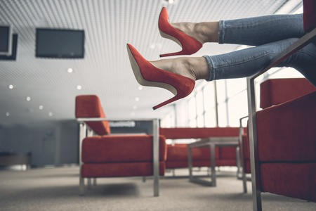 Close up female legs lying on cozy sofa in room for relaxing