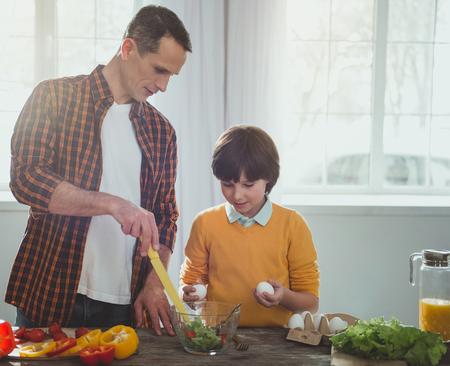Padre e hijo de pie en la mesa de la cocina. Padre apuntando al cuenco con verduras, niño atento sosteniendo huevos
