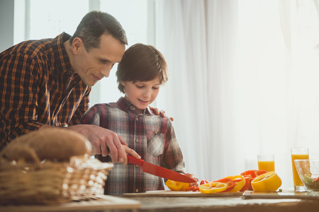 Father and son holding one knife for two and slicing bell peppers. Copy space in right side Stock Photo
