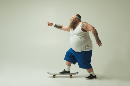 Wait for me. Side view of excited fat man is skateboarding fast. He is looking forward with aspiration. Copy space