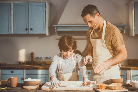 Man and boy standing in kitchen in aprons. Child rolling out batter while father controlling process Stockfoto