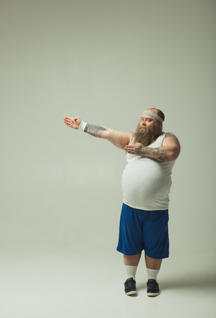 Do sport and do not be like me. Full length portrait of confident fat man pointing aside by hands. Copy space in left side 写真素材