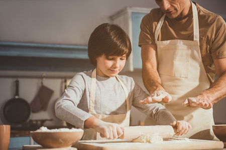 Father and son enjoying cooking together. Boy rolling out dough while man controlling operation