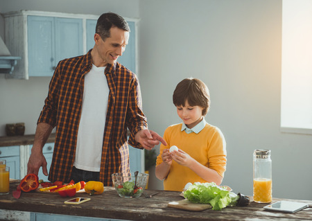 Happy dad and kid standing at the desk with vegetables. Man pointing at egg in child hands