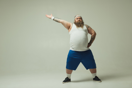 Do sport. Full length portrait of severe fat man showing by hand aside while standing with arm akimbo. Copy space Banque d'images - 100917418