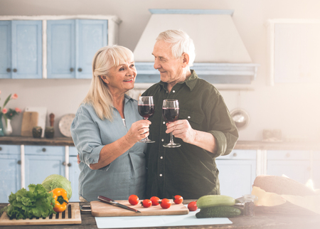 Still love you. Portrait of happy senior man and woman looking at each other with fondness while drinking red wine. They are standing in kitchen during healthy food preparation Foto de archivo - 100917426