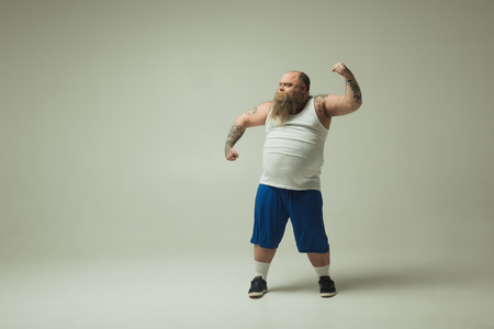 My strength is in my fat. Self-assured male fatso is posing in sportswear. He is straining hand muscles with confidence. Copy space Stock Photo