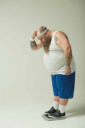 Sad thick bearded guy is weighing on balance. He is looking at result on with frustration. Copy space