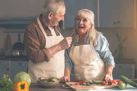 Portrait of happy mature husband is feeding his wife by fresh vegetable. They are sharing one headphone while listening to music in kitchen