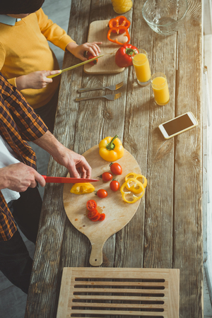 Top view of dad and kid cutting veggies for healthy salad on wooden table. Close up Stock Photo