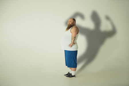 Side view of glad fat man is dreaming of muscular figure. He is standing and looking at camera with confident while his shadow is slim and strong. Copy space