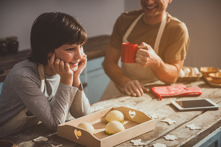 Happy man and boy preparing sweets in cooking room. Adult holding cup. Tray with jelly and dough are on desk. Focus on child