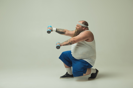 Constrained fat man is lifting dumbbells with effort while squatting. Copy space