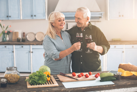 Portrait of glad senior husband and wife celebrating their anniversary in kitchen. They are clinking wineglasses and smiling