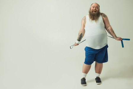 Portrait of playful lazy male fatty holding a jumping rope and laughing. Copy space Banco de Imagens