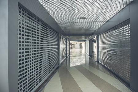 Design of long grey hallway with dark walls and colorful floor