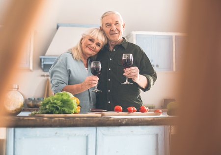 Always happy together. Portrait of happy senior man and woman embracing with love and smiling. They are drinking red wine while cooking together in kitchen