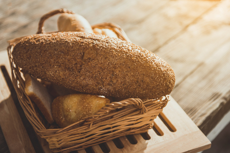 Wicker basket with fresh and delicious bread on timber desk. Close up Stok Fotoğraf