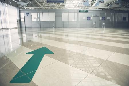 Big green arrow pointant vers la porte fermée blanc en position sur le sol multicolore dans l & # 39 ; hôtel hall Banque d'images - 101023055