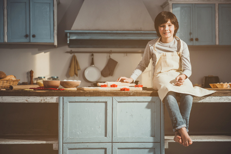 Glad boy taking seat on kitchen desk. He is touching rolling pin and looking at camera with smile. Cooking inventory and ingredients are on table