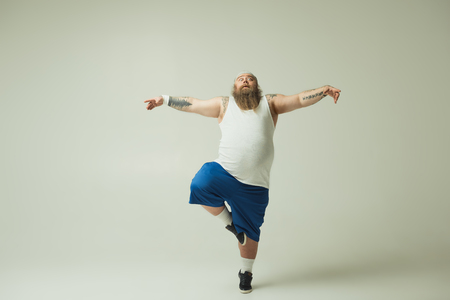 Crane position. Full length portrait of calm thick guy standing on one leg while stretching arms sideways with grace Stock Photo
