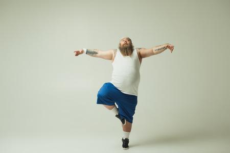 Kraanpositie. Volledig lengteportret van kalme dikke kerel die op één been staat terwijl hij de armen zijwaarts met gratie strekt