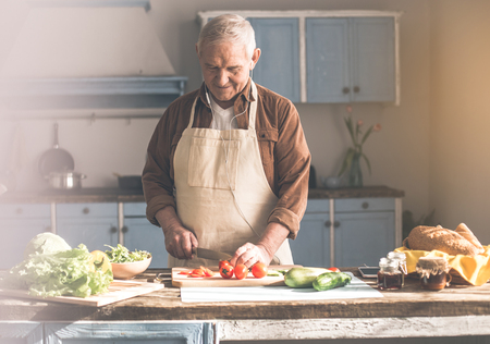 Portrait of relaxed senior man preparing healthy lunch in kitchen. He is listening to music form headphones and smiling Stock Photo