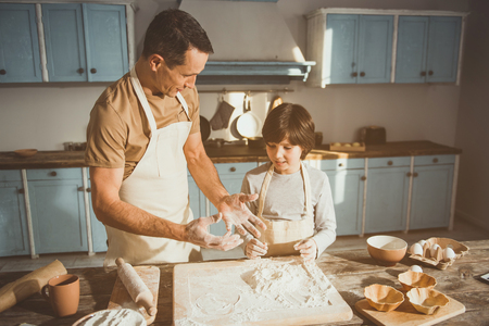 Man and boy standing in kitchen. Dad is speaking and gesturing. Cooking equipment and ingredients are on table