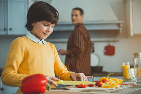 Little boy chopping veggies with pleasure at the table. Father watching him on background